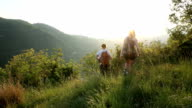Young couple hike through meadow with backpacks at sunrise video