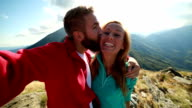 Young couple hiking, taking a selfie on mountain peak video