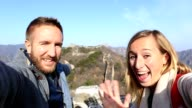 Young couple hiking the Great Wall of China taking selfie video