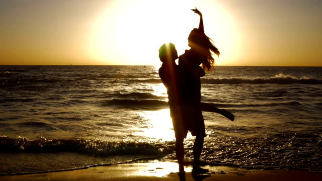 Young couple holding hands and spinning on beautiful ocean beach at sunset. video