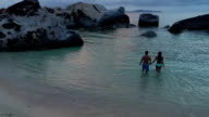Young couple holding hands at tropical beach, Virgin Gorda video