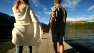 Young couple holding hands on lake pier video