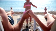 Young couple holding hands on the beach. Their daughter runs to the sea. video