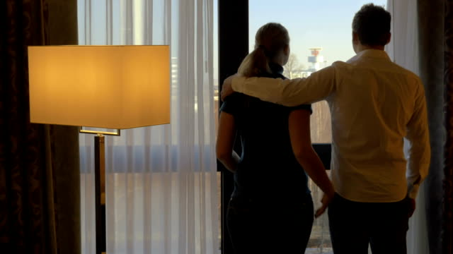 Young couple hugging and looking out the window video