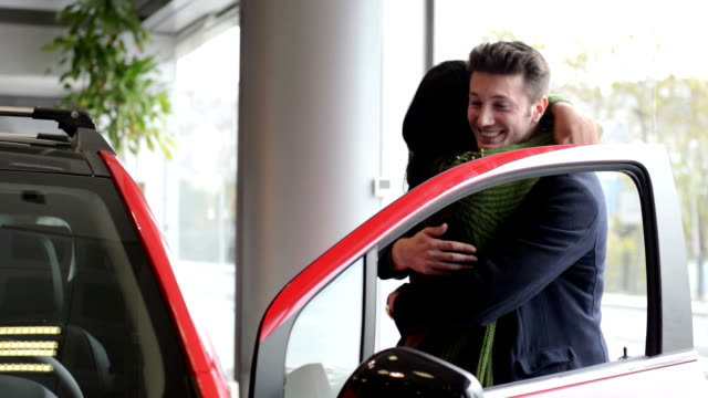 Young couple in a car dealership video