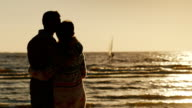 Young couple in love, hugging, looking at the sea and the sunset. Sea sailboat floats. Back view video