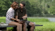 Young couple in nature look at tablet seated on lake jetty in summer day outdoor - HD video footage video