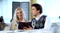 Young couple in restaurant reading menu video