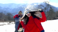 Young couple in snowfight on mountain-slowmotion video
