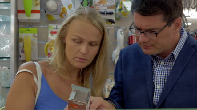Young couple in the section of kitchen utensils video