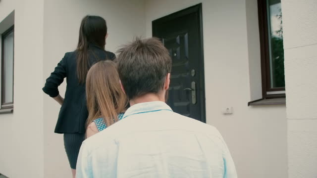 Young couple is following a chatty brunette to the front door of a big white house. Slow motion, Steadicam shot video