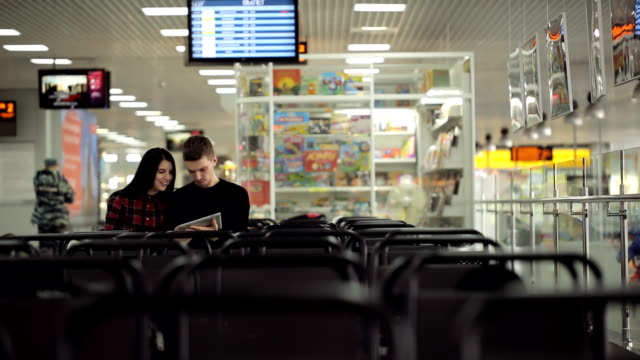 Young couple is sitting in airport waiting area video
