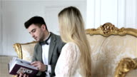 A young couple is sitting on a vintage sofa looking through a photo album. video