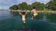 Young couple jumps into the sea from a boat video