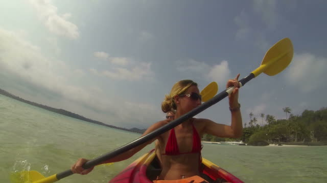 Young couple kayaking in tropical waters video