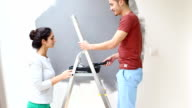 Young couple kissing and painting wall with paint roller video