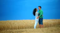 Young couple kissing in a field. Young woman hugging a caucasian man in the middle of a wheat field and kissing each other. video