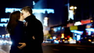 Young couple kissing on the background of the city at night and blurry lights sets video