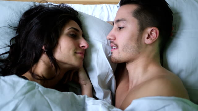 Young couple kissing while lying on bed video