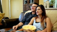 Young couple laughing as they watch TV and eat popcorn together video