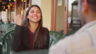 A young couple laughing in slow-motion outside of a downtown cafe video