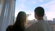 Young couple looking at big city through the window video