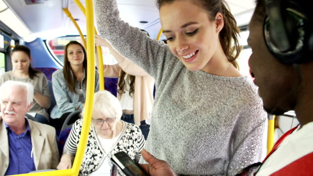 Young Couple Looking At Mobile Phone On Crowded Bus video