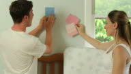 Young couple looks at paint swatches in the baby's room video