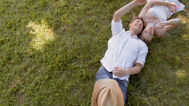 CS Young couple lying on the grass and making bubbles video