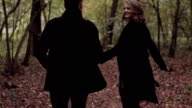 Young couple man and woman running in autumn forest. Slow motion video