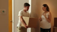 Young couple moves boxes into their new home video