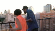 Young couple on a balcony in the early evening video