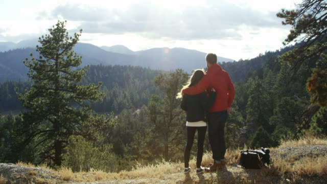 Young couple on a road trip admire the view and take selfie, shot on R3D video