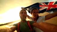 Young couple on beach take selfie portrait with Australian flag video