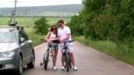 Young couple on bicycles near car with roof-mounted bike carrier video