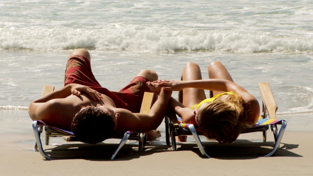 Young couple on lounge chairs holding hands by the ocean video