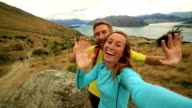 Young couple on mountain take a self portrait video
