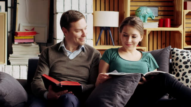 Young couple on sofa reading books, cuddling and having fun video