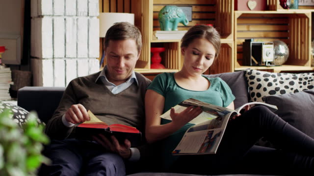 Young couple on the couch reading together and spend family night video