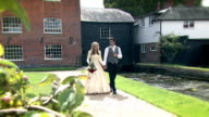 Young couple on their wedding day walking and kissing video