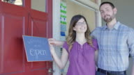 Young couple opening their small business holding a 'We Are Open' sign video