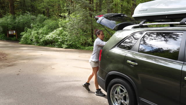 SLO MO young couple packing up car after backpacking trip video