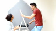 Young couple painting wall with paint roller video