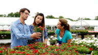 Young couple pick out flowers for their garden video