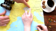 Young couple planning honeymoon vacation with map video