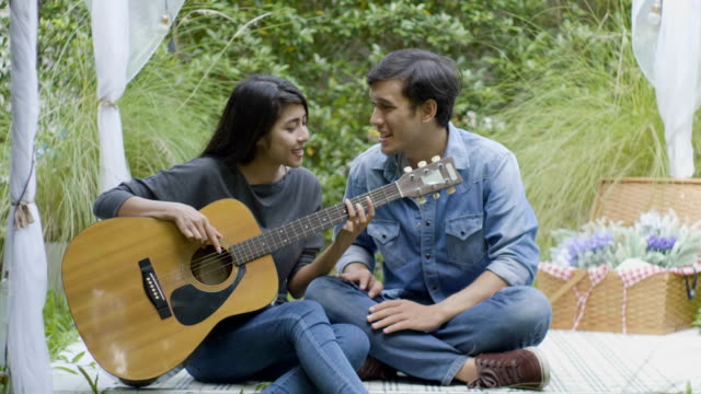Young couple playing guitar at the park video