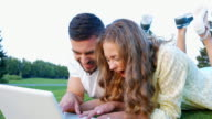 Young couple playing in games on laptop. video