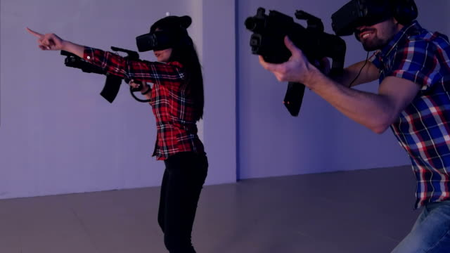 Young couple playing VR shooter game with virtual reality guns and glasses video