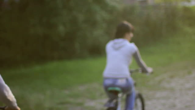 Young couple pleasure ride bicycles in park, man romantic woman video