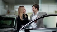 Young couple rejoicing buying a car video